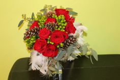 Winter wedding bouquet of red roses, green hypericum berries, pinecones, seeded eucalpytus and white roses by Beautiful Blooms by Jen.
