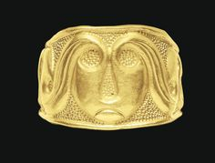 A CELTIC GOLD FINGER RING   CIRCA 4TH CENTURY B.C.   Formed from hammered sheet, the narrow overlapping ends soldered together, the entire length embossed with a scrolling vegetal motif, the background stippled, the larger central zone filled with a scroll that doubles as a stylized facing head with circular eyes, a drop-shaped nose and an incised downturned mouth, the flanking scrolls serving as the hair, the strands incised