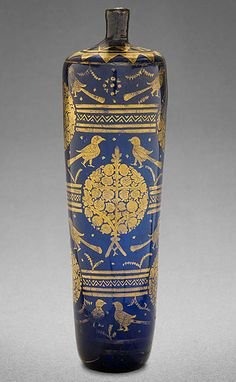 This gilded blue flask was made in or near what is today the small Syrian city of Raqqa. In the mid-12th century AD, the city was a thriving centre for the production of pottery & glass. The gold was applied to the body of the bottle in thin sheets before the designs – birds flanking a pomegranate tree, evoking both earthly & heavenly gardens – were scratched in.