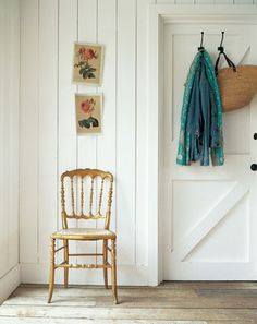 love this simple chair, clad white walls, barn door, bare floorboards, hooks and baskets, simple vintage style