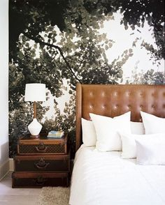 cognac leather tufted headboard, accent wall, vintage suitcases as nightstand