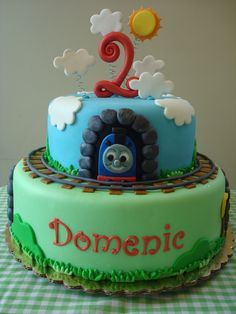 "Thomas the Train Cake - ""Thomas the Train"" cake! Happy 2nd Birthday, Domenic!  2 tier marshmallow fondant covered cake (8 & 12 inches). Each tier is vanilla cake filled with chocolate chip vanilla cream and crumb coated with vanilla buttercream.  Marshmallow fondant train, tunnels, rocks, grass & tracks. Gumpaste #2, clouds & sun."