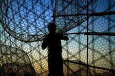 Malkiya, Bahrain: a fisherman works on fish traps at sunset Photograph: Hasan Jamali/AP