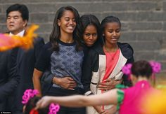 First mother: U.S. first lady Michelle Obama (C) hugs her daughters Malia (L) and Sasha (R) as they watch a folk dance by performers during ...