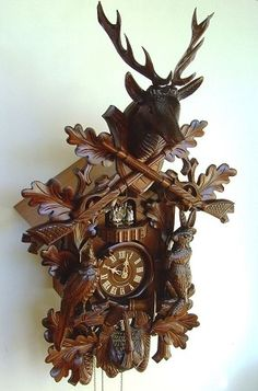 """Model #8TMT 295/9 Musical Hunters Cuckoo Clock with live animals  •Musical Hunters cuckoo clock with live animals (upright)   •29"""" x 17"""" W x 15.5"""" D  •German Regula, 8 day movement (must be wound weekly)  •Music box plays one of two melodies, after the call of cuckoo, at the top of the hour.  •Hand-carved  •4 Hand-carved dancing figurines  •Wooden dial  •Wooden hands  •Wooden cuckoo bird  •Night shut-off switch   •Antique stain  •Made by Anton Schneider  •2 Year warranty"""