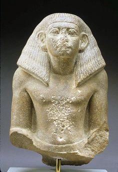 Statuette of an official, dynasty 12, 19th century BCE, from the Memphite region (upper Egypt), quartzite, elaborate wig. Metropolitan Museum