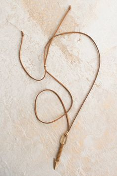 Hammered arrow pendant on a brown suede necklace.