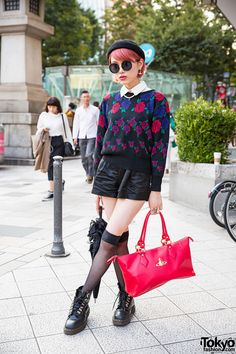 Tokyo Fashion 19-year-old Mizuki on the street in Harajuku with pink hair and a beret, a San-biki no Koneko sweater, shorts, Dr. Martens, and a Vivienne Westwood bag.