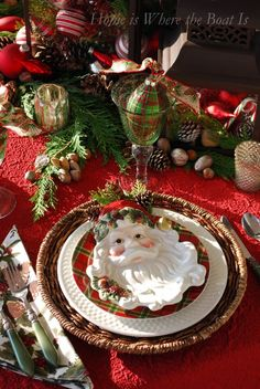 Old St. Nick, plaid, and lanterns filled with ornaments, pine cones, nuts and greenery, and for additional merry measure, some candy canes. #Christmas #table