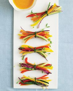Small slivers of vegetables tied with edible chive ribbons with a tangy carrot-ginger dipping sauce