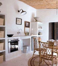 Une cuisine authentique avec meubles en béton et mobilier en rotin