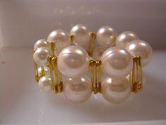 Pulsera elástica hecha con perlas e imperdibles dorados.