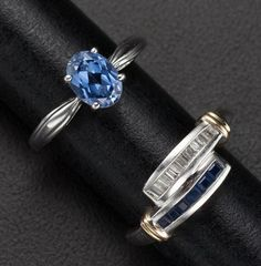 A beautiful pair of sapphire, diamond, and white gold rings, one featuring an oval-shaped sapphire set centrally, the other featuring diamonds and sapphires set in two bands across the top of the ring.