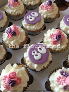 Birthday cupcakes with pretty pink and purple flowers.