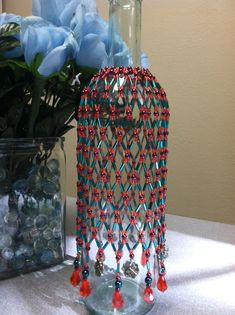 Beaded Wine Bottle cover made with red, teal, purple and dragonfly charms 2013. Sold