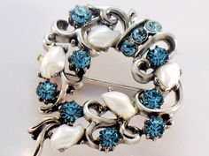 Vintage Lisner Blue Rhinestone and Faux Pearl Brooch by JewelryQuestDesign.  Exquisite Condition Signed Lisner Blue Rhinestone and Faux Pearl Brooch Pin in silver tone. 11 Blue Faceted Rhinestones and 5 Faux Pearl are set in this silver toned pin, styled in a traditional round with scroll work. It measures about 1.5 inches in diameter and is in near mint condition. A lovely piece of vintage jewelry.