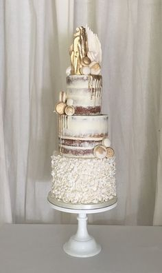 Stunning semi naked wedding cake. Adorned with white chocolate and gold shards, macaroons and gold drip.