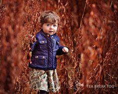 Little girl peeking out of some golden reeds.
