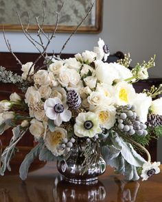 David Austin's 'Patience' white garden rose mingle with bright-faced anemones, soft pink majolica spray roses, tiny green berzillia berries, and fuzzy little pompons of brunia. The silvery leaves of dusty miller, elegant lichen branches, faux-snow-dusted pinecones, and sprigs of lacy Leyland cypress fluff and fill in. - Seven Floral Arrangements for Winter - www.southernladymagazine.com