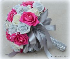 Brides bouquet of roses in hot pink, silver and ivory foam roses with brooches and rhinestone handle
