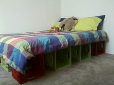 Kid's Bed! Old milk crates (12 total) painted with plastic bonding paint, grip shelf liner, ply board, and futon mattress. Easy bed with built in storage!