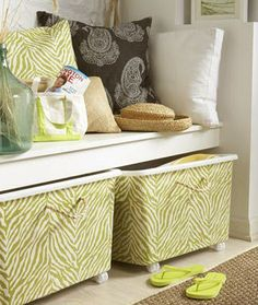 Plain plastic storage bin covered with fabric or paper and Mod Podge. With wheels & rope handles added they fit into the décor instead of in a closet