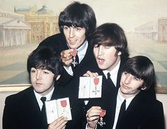 The Beatles show off their MBE (Member of the British Empire) medals, given to them by the Queen for promoting England in their music. John would send his back in protest in 1969, and Paul would later be knighted for charity work