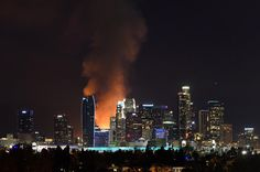 Hundreds of firefighters battled to contain a huge fire at an under-construction apartment complex in downtown Los Angeles early Monday. Flames and smoke fro...