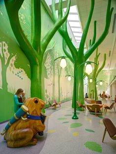 """At Nationwide Children's Hospital in Columbus, Ohio, the """"Magic Forest"""" offers a wonderland of giant trees and animals brought to life by sounds of chirping birds and other forest noises to transport visitors away from the hospital environment. Lighting changes among the forest elements help maintain the magic of the space around the clock. Photo: ©Brad Feinknopf."""
