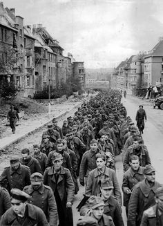 German prisoners, captured during the fall of Aachen, marching through the ruined streets, October 1944. [[MORE]] realtaylers: This picture was taken during the Battle of Aachen, one of the largest...