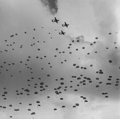 Some of the 8,000 paratroopers dropping into the drop zone from air transports. Elevation of planes at about 800 feet to 1000 feet. A point of interest- there were no fatalities during the entire day.