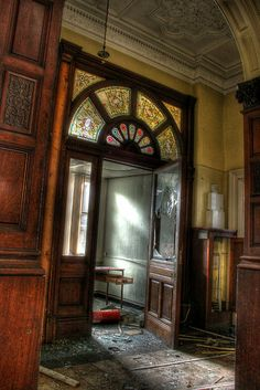 What remains of a once elegant main entrance door of an abandoned mansion.