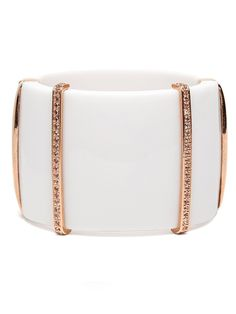 This chic wide bangle works a stylish tusk-chic vibe cast in ivory resin while the bands of Swarovski crystals and rose gold bring a touch of opulence.