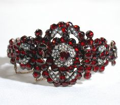 Bohemian garnet bracelet. Mounted in the rose gold gilding over silver, clusters of faceted garnets have been accented with tiny half seed pearls. Circa 1860.