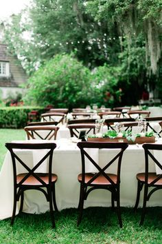 Outdoor estate reception with cafe lights and x back wooden chairs. | Debra Eby Photography Co.