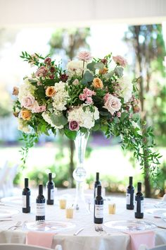 Tall floral centerpiece. Garden style centerpiece. blush, gold, white, rose flowers with lots of greenery. Personalized wine bottles for favors all make this reception area amazing Personalized Wine Bottles, Reception Areas, Rose Flowers, Floral Centerpieces, Garden Styles, Greenery, Favors, Blush, Table Decorations
