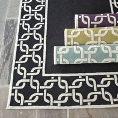 Santorini Indoor/Outdoor Rug:   The linked chain border adds pattern with plenty of colorful open ground for furniture. Hand hooked in a loop construction of washable, poly-acrylic pile that's soft underfoot, but durable enough for outdoor living. To clean, just wash with mild soap or rinse with a hose.