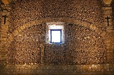 """Human skulls forming an arch framed by leg bones in the Chapel of Bones (Capela dos Ossos) in Evora, Portugal. The inscription at the entrance to the chapel reads, in translation, """"We, bones that lie here, for yours await"""". This is only one wall. The decorations in bones run around all the walls, over the ceiling and down columns, using various sizes of human bones for patterning."""