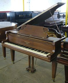 An Eavestaff baby grand piano with a satin, mahogany caseand square tapered, legs at Besbrode Pianos.