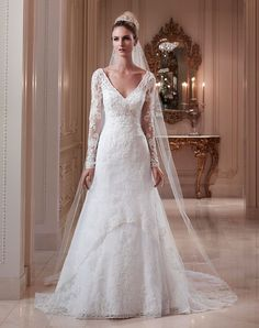 "This gown features a ""V"" front neckline with sheer long sleeves and a demure key hole back. Beaded lace overlay is accented with a beaded appliqué on the ..."