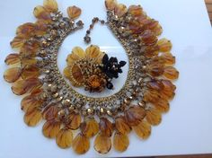 Rare bib Haskell necklace and Lawrence VRBA brooch which uses the same large flat amber-color beads as the Haskell necklace. The beads are wired to brass-toned metal. It has the classic Haskell beaded flower hook clasp which is signed. The necklace length at the throat is 16 inches.