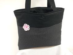 Shopper aus schwarzer Baumwolle mit einer aufgenähten rosa Häkelblüte. Geschlossen wird die Tasche mit einem Druckknopf.