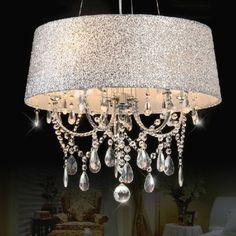 Crystal droplets cascade gently on a candelabra fixture surrounded by a shiny silver fabric shade.