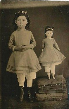 Stand by me | Circa 1870 tintype features identically dressed and coifed girl and doll.  Doll has earrings, china hands, feet.