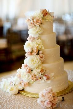 Cascading, full-petaled flowers by Yvonne Design add romance to this towering five-tiered cake.  Photo by Frank Amodo.