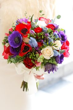 Vibrant #bridal bouquet of purple and red anemones, roses, freesia and fragrant muscari.