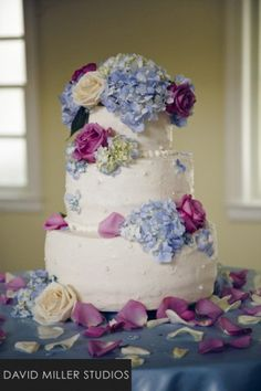 Photo of a floral decorated three tier round wedding cake sitting on top of a light blue table cloth with lavender and white rose petals strewn around. Light blue hydrangea and lavender and white roses adorn the top tier of the cake while a small cluster of light blue hydrangea and a lavender rose bud sit at the edge of the second and third tier.