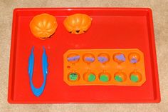 Halloween Montessori activities: Using easy grip tweezers to transfer Halloween-themed erasers into a pumpkin-shaped ice cube tray || Gift of Curiosity
