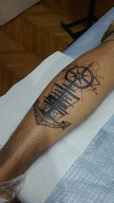 Tatuagem na panturrilha de um navio com uma bússola acima dele e uma âncora abaixo.