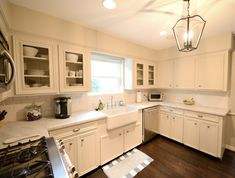U shaped kitchen design with honed carrara marble countertops, creamy white kitchen cabinetry and porcelain farmhouse sink. Cream And White Kitchen, Off White Kitchens, Brown Kitchens, Cream Kitchens, Cream Kitchen Cabinets, Off White Cabinets, Hardwood Floors In Kitchen, Kitchen Flooring, Wood Flooring